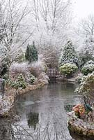 Evergreen garden in winter with hoar frost with lake - Lift the Latch, Somerset