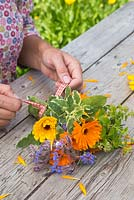 Woman creating a floral bouquet of Calendula officinalis 'Art Shades', Sage and Borage