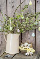 Decorative eggs hanging from fresh spring foliage, accompanied with a bowl of Quail eggs