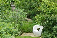 A view over the garden with its winding paths and sculptured seat. Plants include: Sumack, Betual utilus, Olea Europaea, Magnolia, Thalictrum and Euphorbia. Seat by Solid Soul Furniture Designs.