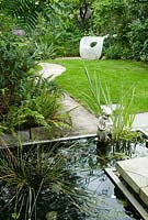 A view over the pond down the garden path.  Plants include: Ferns, Hellebore foliage, Sumach, Foxgloves and white roses.