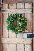 Christmas wreath with dried fruit and cinnamon bundles mounted on a door.