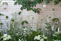 Birdboxes, insect hotels, bird feeders and white and green planting in Living Landscapes: City Twitchers garden at Hampton Court Palace Flower Show 2015