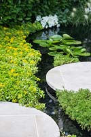 City Twitchers Garden, view of concrete circular stepping slabs over a pond and a stream with stone bottom surrounded by Chamaemelum nobile and  Sedum carpet. - Designer: Sarah Keyser, Sponsor: Living Landscapes