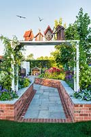 Just Retirement: A Garden For Every Retiree, view of white pergola with birdhouses and birds at the entrance to rural garden. Designer: Tracy Foster Sponsor: Just Retirement Ltd