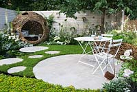 City Twitchers Garden -  view of woven willow bird hide and seating area with metal white furnitures and stone - concrete circular slabs as a path over a pond surrounded by Chamaemelum nobile - chamomile lawn and Sedum carpet.