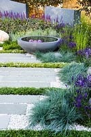 Patio with wooden bench and circular concrete water feature amongst Festuca glauca, Thymus, Lavandula, Nepeta. H U G: Healing Urban Garden. Designer: Rae Wilkinson. Sponsor: Living Landscapes