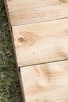 Building wooden compost bin, step by step. detail of planks secured to main support