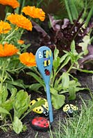 Painted wooden spoon to indicate a child's garden, with pebbles painted as ladybirds.