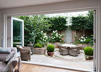 Walpole Gardens: London. View through folding patio doors onto brick walled garden and sunken circular brick and tile patio. Betula utilis 'Jacquemontii', Hydrangea arborescens 'Annabelle', Carpinus betulus, Buxus sempervivens, Heuchera 'Rave On', Erigeron karvinskiansus
