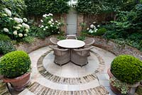 Walpole Gardens: London. View onto circular tile and brick sunken patio with Carpinus betulus, Hydrangea arborescens 'Annabelle', Salvia 'Caradonna', Erigeron karvinskiansus, Heuchera 'Rave On', Buxus sempervivens