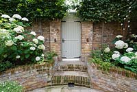 View from circular sunken patio onto brick steps and garden door with garden wall stone head sculpture and uplighting. Carpinus betulus, Hydrangea arborescens 'Annabelle'