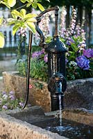Vintage hand water pump over stone sink by JS Gardens