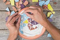 Pushing Mosaic pieces into adhesive