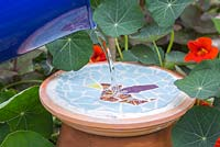 Filling the mosaic bird bath with water