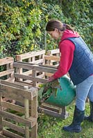Woman adding garden waste to a Three Bin Composting system constructed from Upcycled wooden pallets