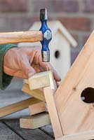 Secure the wooden batons to the roof of the bird house using a hammer