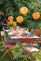 Party in the garden. Orange lanterns as decoration: Bouquet of calendula, Helenium and Alchemilla