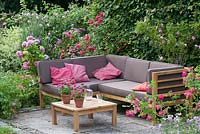 Corner sofa on a small terrace surrounded by roses, behind is a hedge of Carpinus - hornbeam as a screen