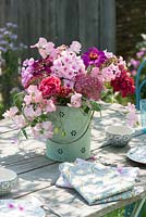 Table laid with display of Phlox paniculata, Lathyrus odoratus, Zinnia, Hydrangea 'Bella Anna' and Achillea
