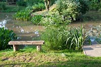 Rustic wooden bench overlooking landscaped lake in country garden with jetty. Bradness Gallery, East Sussex. Owners: Artists Michael Cruickshank and Emma Burnett