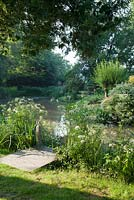 Wooden jetty alongside landscaped lake in mature country garden in summer. Bradness Gallery, East Sussex. Owners: Artists Michael Cruickshank and Emma Burnett