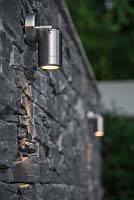 View of lighting features against a dry stone slate wall