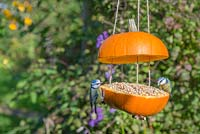 A pair of blue tits eating seed from the Pumpkin Bird Feeder