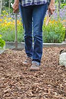 Woman walking down path of bark chippings mulch carrying garden tools