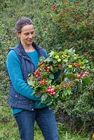 Woman holding an Autumnal Berry wreath featuring Wild Crab Apples, Hawthorn - Crataegus, Sloe berries - Prunus spinosa, Rose hips, English Oak - Quercus robur and Crocosmia seed heads