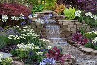 the waterfall in the centre of 'The Water Garden' at RHS Tatton Flower Show 2015, bordered by dense, colourful planting