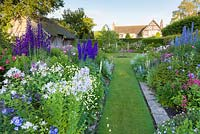 Early morning in the Sundial Garden, looking towards the 16th century house at Wollerton Old Hall Garden, Shropshire. Planting includes - Campanula lactiflora, Delphiniums, Phlox paniculata, Stachys and David Austin roses. Photographed in July