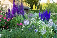 Shortly after dawn in the Sundial Garden at Wollerton Old Hall Garden, Shropshire - July. Planting includes David Austin roses, Delphiniums, Phlox paniculata and Campanula lactiflora. Beyond can be seen the pyramidal yews of the Yew Walk