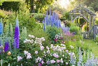 Shortly after dawn on a misty morning in the Sundial Garden at Wollerton Old Hall Garden, Wollerton, Shropshire - featuring David Austin roses, Stachys, Delphiniums, Dahlias, Phlox paniculata, Salvia microphylla and Knautia, among a wide range of other herbaceous plants.