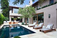 View of modern swimming pool with outside seating area sun loungers and mature olive tree.