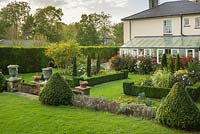 View of formal country house garden in late summer. Box edging and topiary, fastigiate yew trees trimmed to shape. Display of dahlias beside conservatory. Lead urns with echeverias.