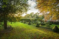 View of formal country house garden in late summer. Box edging and topiary cones, fastigiate yew trees trimmed to shape. Antique stone garden roller propped against ancient box tree.