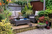 Tucked away in quiet corner at bottom of garden, between shed and greenhouse, a raised wooden deck with outdoor rattan furniture and tabby cat Trixie. Pots with bonsai trees, coleus and ornamental grasses.