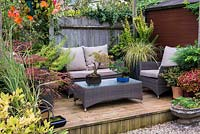 Tucked away in quiet corner at bottom of garden a raised wooden deck with outdoor rattan furniture and containers of acer, bonsai, verbena, coleus and ornamental grasses.