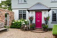Cottage with front door flanked by pair of urns planted with Fuchsia 'Sunray', Salvia 'Black Knight', Pelargonium hortorum 'Orbit Synchro' and pink cosmos. Left bed planted with Hydrangea 'Annabelle' and box hedge. Doorway in brick wall on left leads into small courtyard garden.