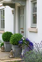 Metal containers with topiary box balls beside a front door. Lavender fills a gravel bed leading along the side of the house.