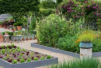 A potager with raised beds of vegetables and flowers, including salad leaves, peas, carrots and marigolds. A stone plith with a copper pot of lavender provides a focal point on the central axis.