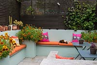 An outdoor room with built in benches and raised beds, planted with Gaillardia. Pet cat asleep