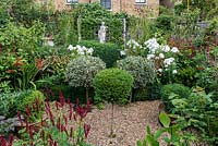 In 12m x 6m town garden, formal parterre with box and variegated holly standards, and box edged beds of Phlox paniculata 'David', Aconitum 'Spark's Variety', salvia, sanguisorba, crocosmia and red or pink persicarias.