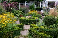 A suburban garden with a circular structure created by shaped box and paving sets. Deep borders of mixed planting includes Astrantia, Rudbeckia, Salvia, Verbena and ornamental grasses.