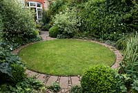 A town garden with circular lawn surrounded by a stone path and foliage plants including Buxus sempervirens balls and Cornus alba 'Elegantissima' shrubs.