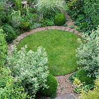 An aerial view of a circular lawn surrounded by a brick path, Cornus alba 'Elegantissima', Miscanthus grass and Buxus sempervirens balls.