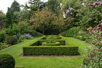 A formal garden with a box parterre, box balls and lawn. At the far end Malus Royalty trees form an arch.