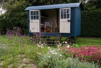 The Shepherd's Hut, a mobile summer house, behind a border of Verbena bonariensis, Anemone x hybrida and Sedum Autumn Joy.