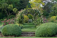 A country garden with rose covered pergola over a grass path.
